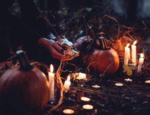 zucche, candele e delle mani che reggono qualcosa